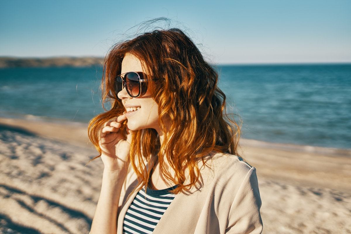 Woman at the beach with salty hair waving in the wind in need of wave quotes & captions for Instagram.