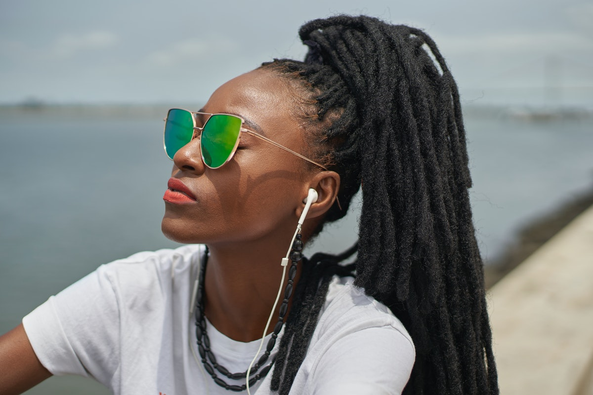 Young woman with green sunglasses looking into the distance to show how her zodiac sign deals with anger.