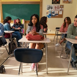 Devi sitting between Paxton and Ben in a classroom at three desks.