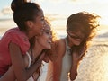 3 young women looking out at the water at the beach, with their salty hair blowing in the wind, watc...