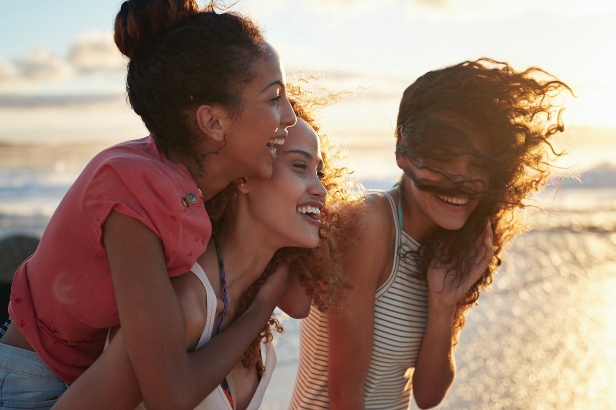 3 young women looking out at the water at the beach, with their salty hair blowing in the wind, watching the ocean waves go by before posting on Instagram with a wave quote or caption.