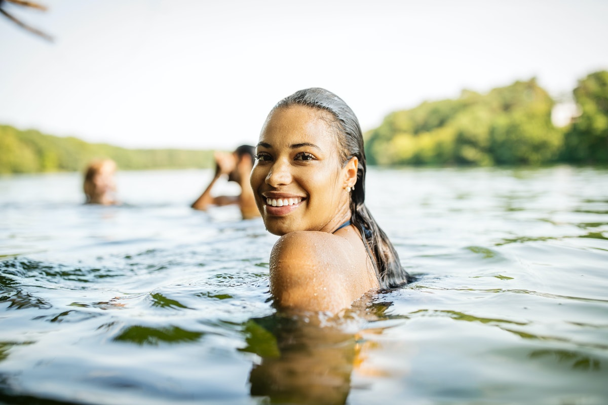 Young woman swimming in a lake with her friends in need of lake captions for Instagram.