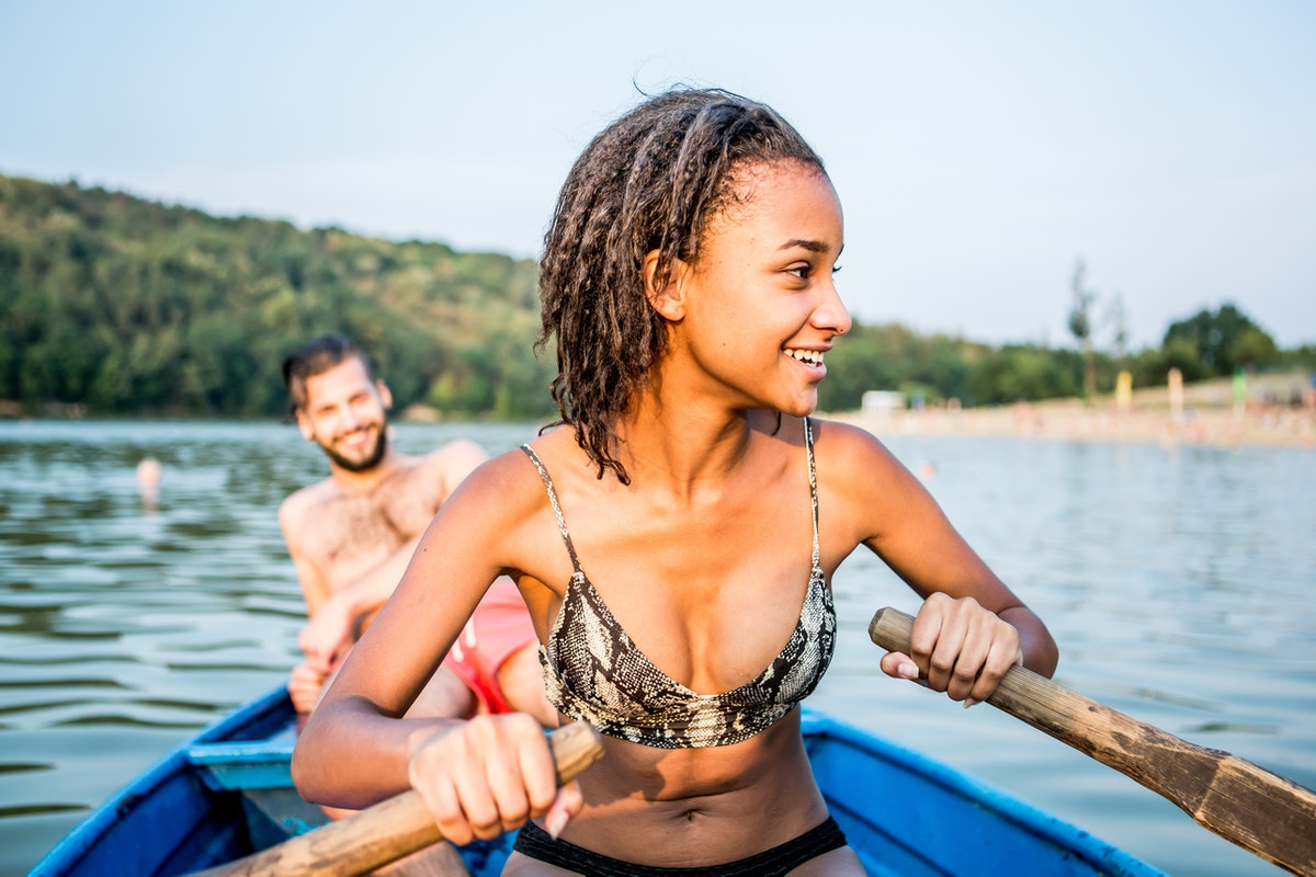 Young woman paddling a boat out on a lake with her boyfriend before posting on Instagram with a lake...