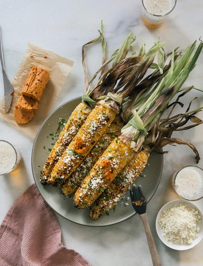 overhead view of corn on the cob, husks on, with chipotle bourbon butter and cheese,