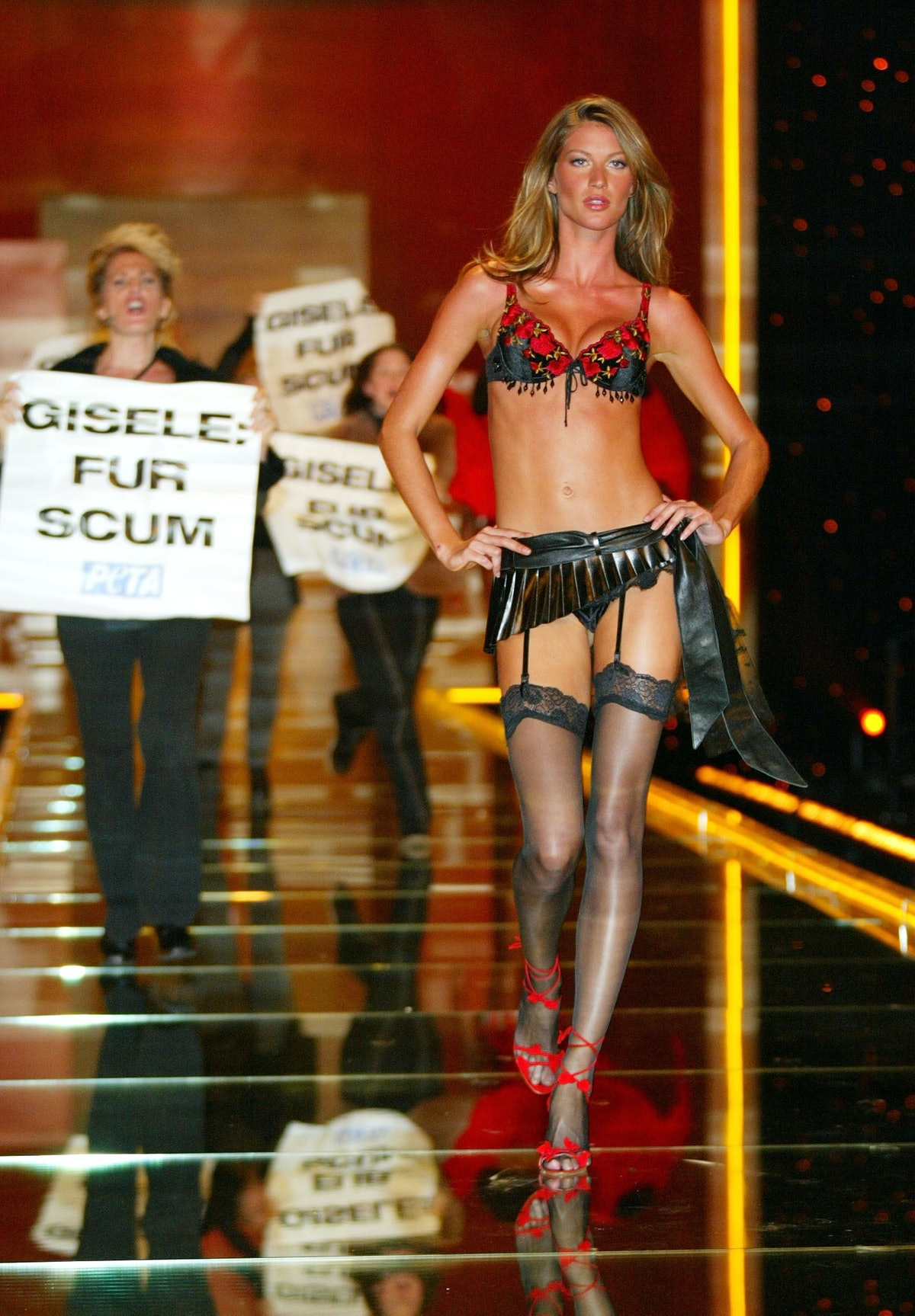 Gisele Bünchen walking in front of protesters on the runway