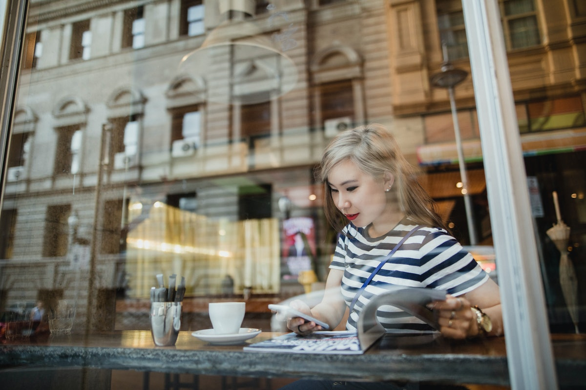 Young woman at a coffee shop writing down a plan to ask for her next raise in her diary.