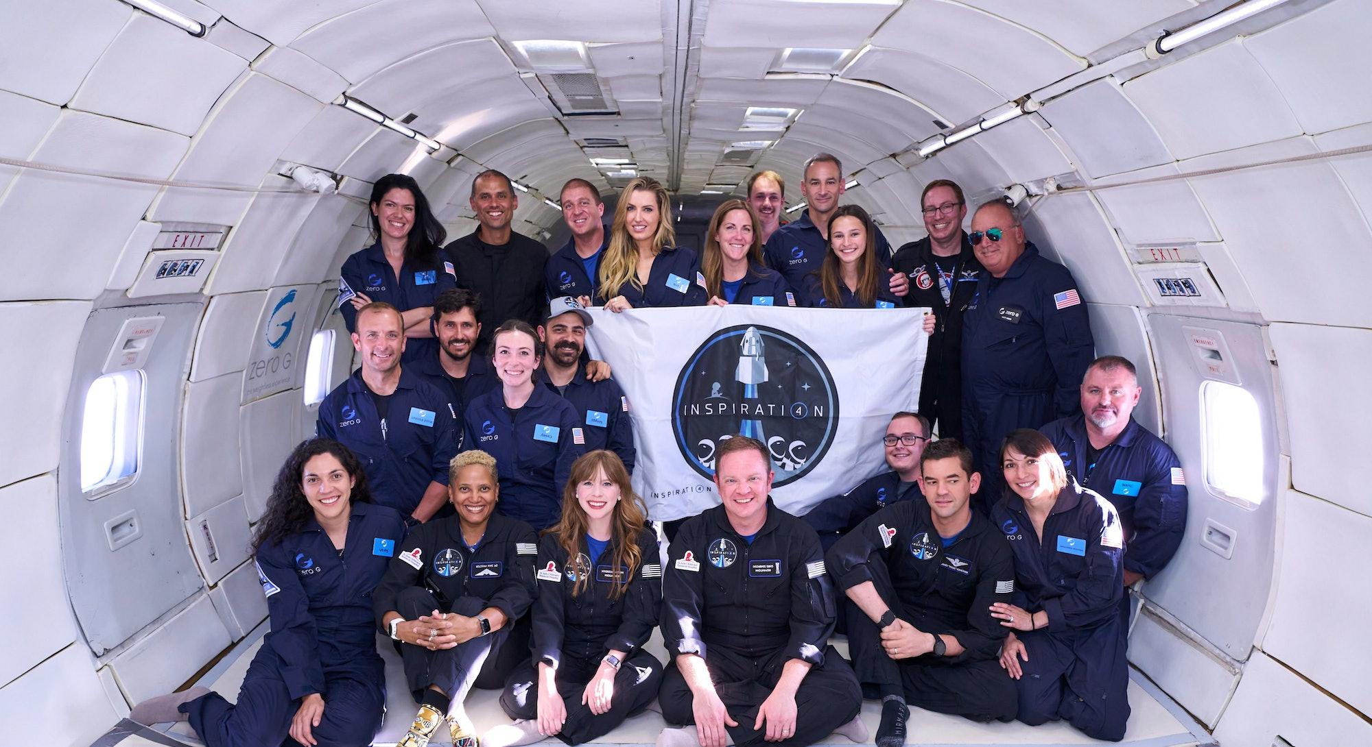 Inspiration4 civilian crew holding mission banner