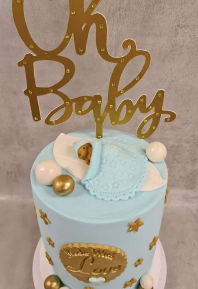 Baby shower cake with sleeping baby on top.