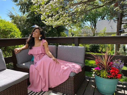 a woman wearing a pink baby shower dress sitting on a bench outside