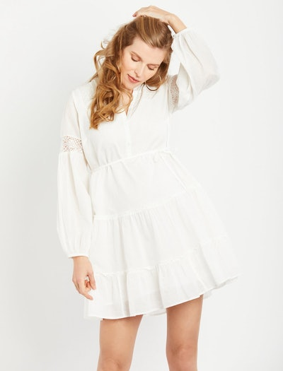a white bohemian style maternity dress with long sleeves and crotchet details in the sleeve