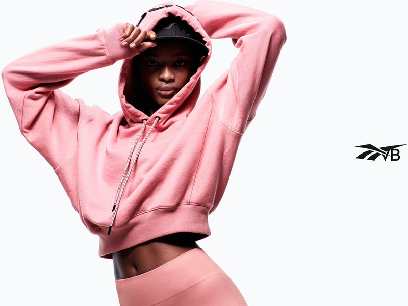 Model wears pink cropped hoodie and leggings from Reebok x Victoria Beckham Drop 5, releasing on Jul...