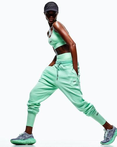 Model wears minty green sports bra, shorts, and sweatpants from Reebok x Victoria Beckham Drop 5, re...
