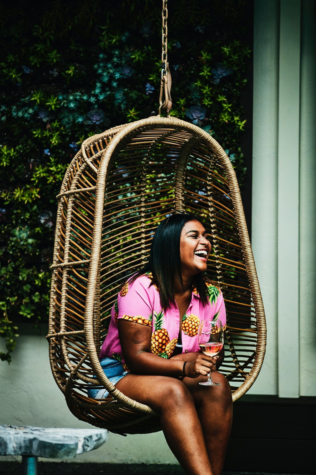 Young woman laughing in a hanging chair, holding a glass of wine before posting a pic on Instagram w...