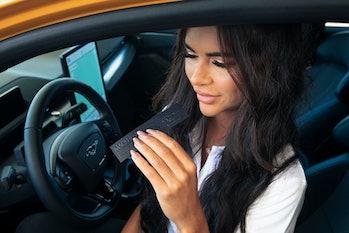 A woman smelling a perfume strip