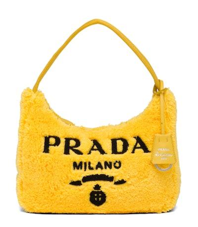 A yellow Prada Re-Edition 2000 bag.
