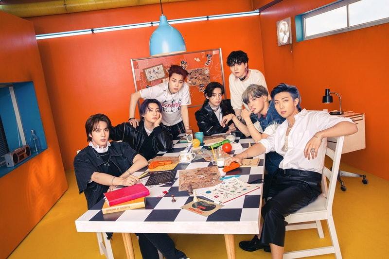 BTS poses together at a table filled with books and cups of tea.