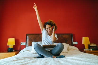 Happy young woman listening to music on her bed, having the best week of July 26, 2021, per her zodi...