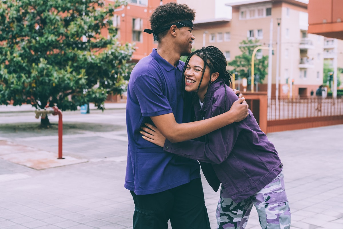 Brother and sister hugging in town square on his birthday, waiting to post on Instagram with a birth...