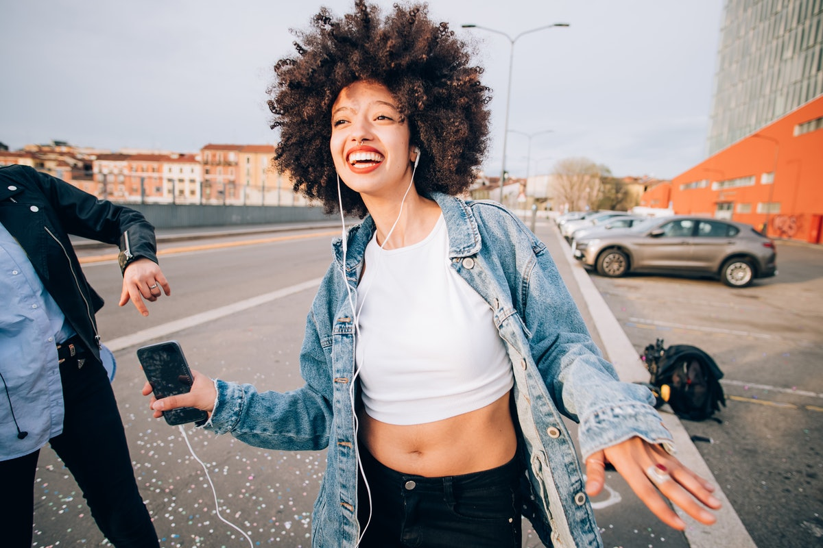 Happy young woman listening to music, having the best August 2021, per her zodiac sign's monthly hor...