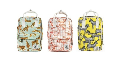 Three backpacks in a row; one with tiger print, one with dino print, one with zebra print