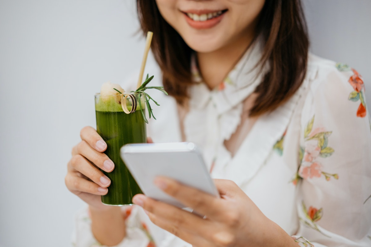 Young woman holding a cup of matcha green tea before posting a pic on Instagram with matcha puns, ma...