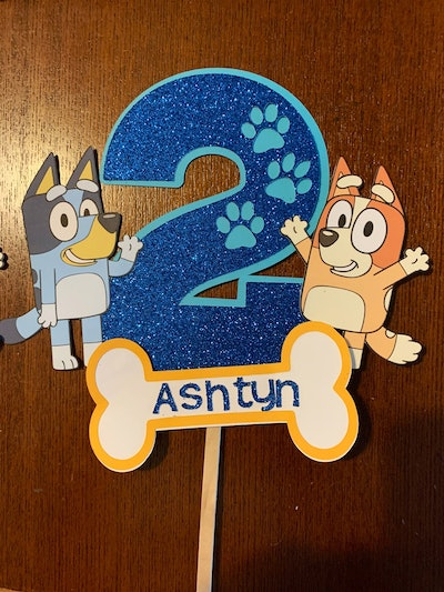 """Cake topper with the number """"2"""" and Bluey and Bingo characters from """"Bluey"""""""