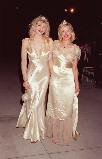 Dressed in similar, silver evening gowns and tiaras, American musician and actress Courtney Love (le...
