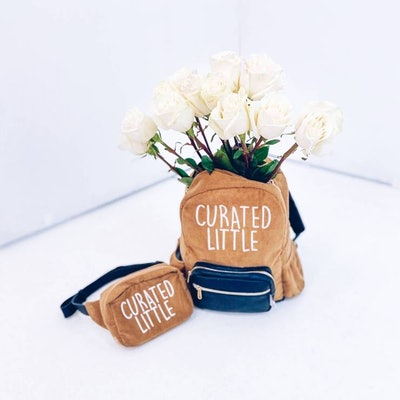 """Brown fanny pack and brown bookbag that say """"curated life""""; bookbag is holding white flowers"""