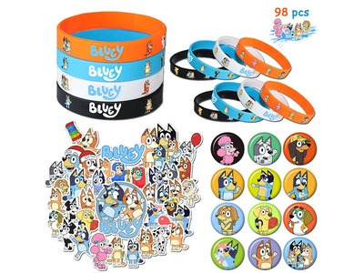 """Piles of """"Bluey"""" themed party favors; bracelets, stickers, and pins"""