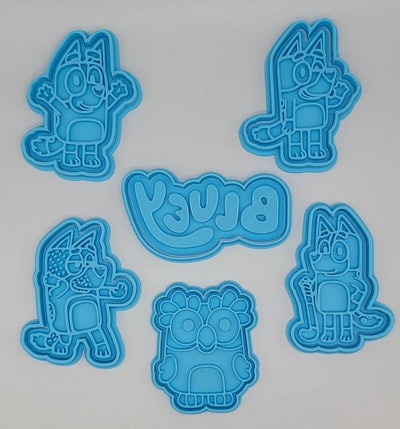 """Six cookie cutters on a table; cutters in the shape of characters from """"Bluey"""""""