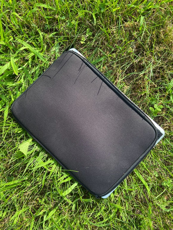 A black laptop sleeve is shown with the corners of the laptop sticking out.