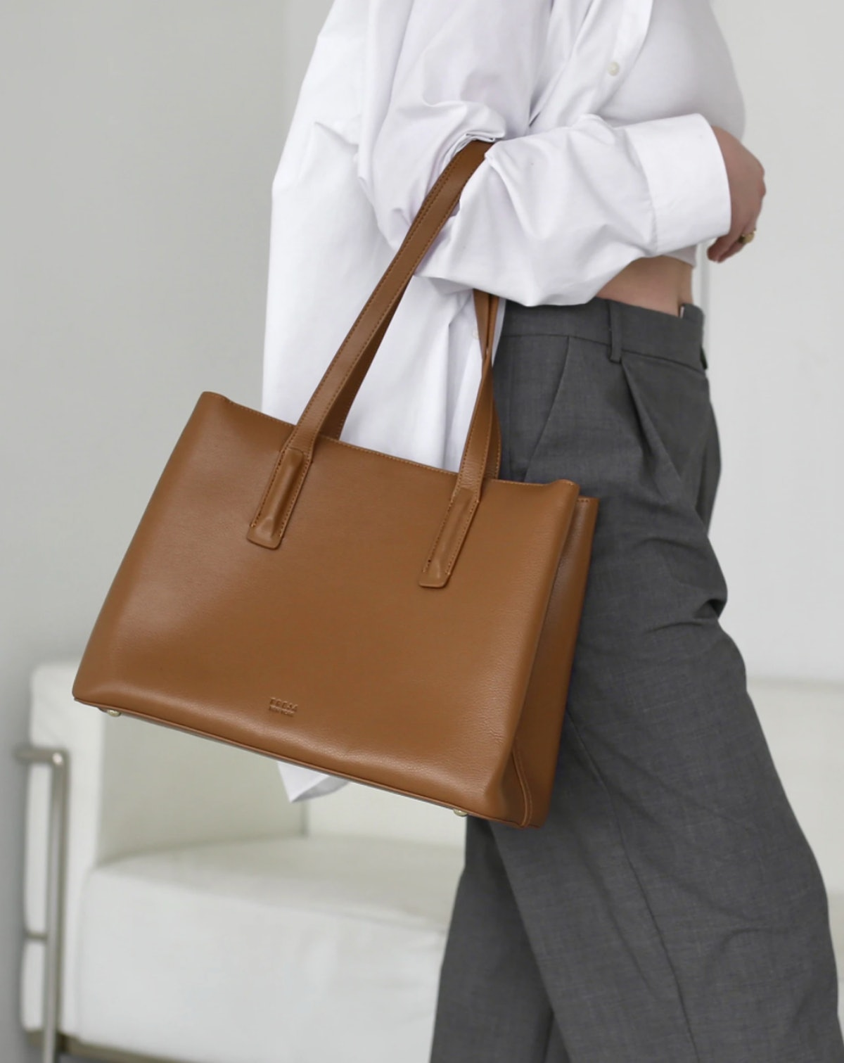 A caramel colored tote bag by Freja New York that can fit a 13-14 inch laptop.