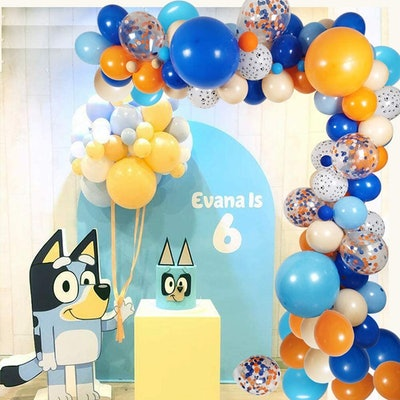 """Birthday party backdrop with """"Bluey"""" character, cake, and balloon arch"""