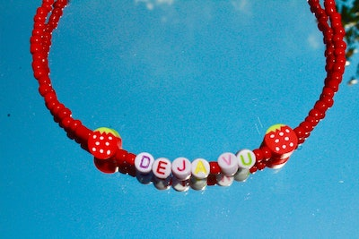 deja vu beaded necklace with red beads and strawberry charms