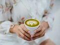 Young woman holding a cup of matcha, thinking of matcha puns, quotes, and captions to post on Instag...