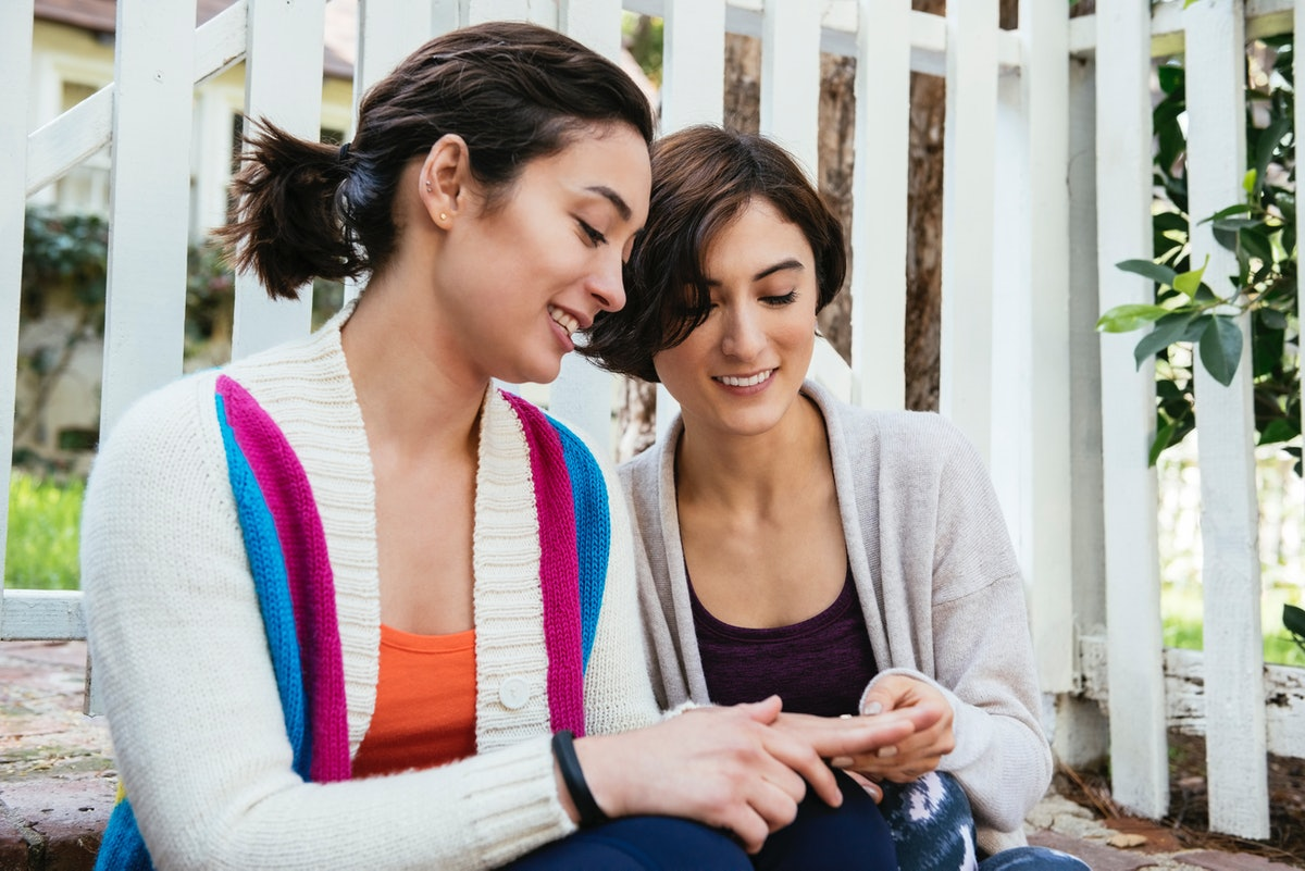 Young woman wishing her sister a happy engagement as she shows off her ring before posting on Instag...