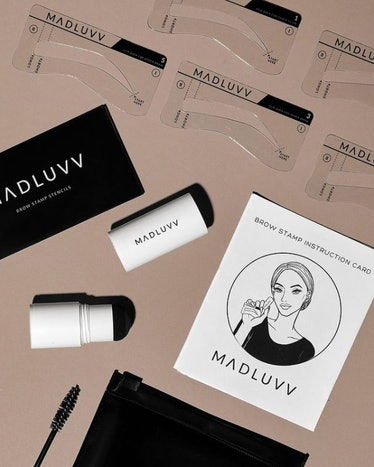 A photo of the contents of Maduvv's Brow Stamp Kit including stencils, brow pomade, and a spoolie.