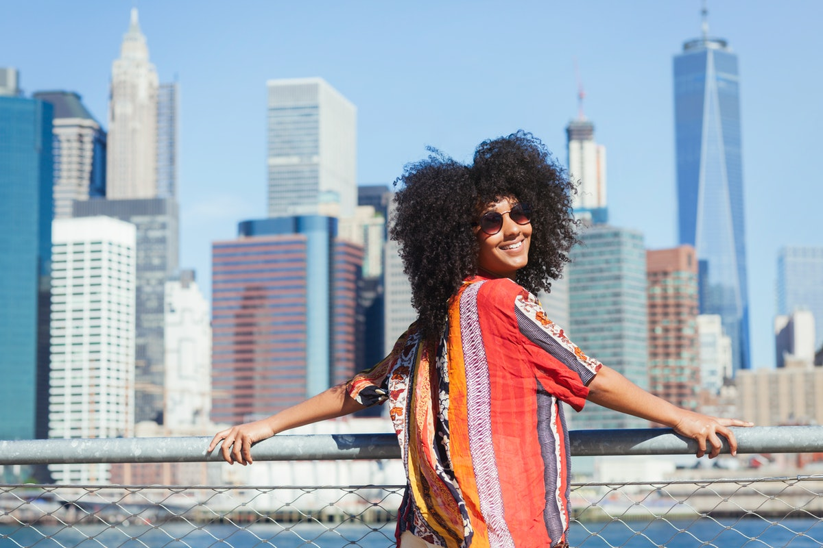 Young woman smiling with the NYC skyline in the background before posting a pic on Instagram with sk...
