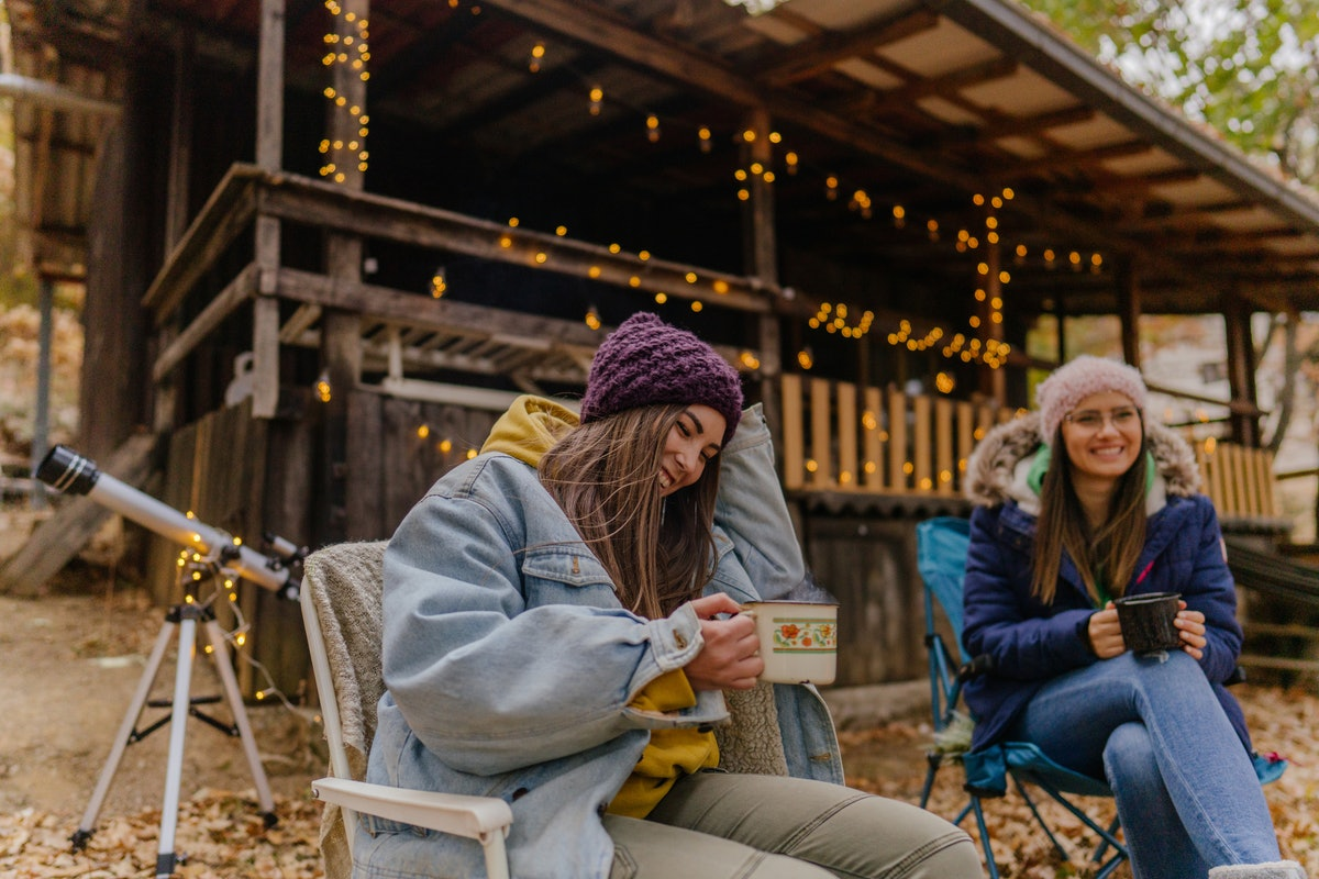 2 young friends drinking hot chocolate at a cabin in the fall before posting a pic on Instagram with camping captions.