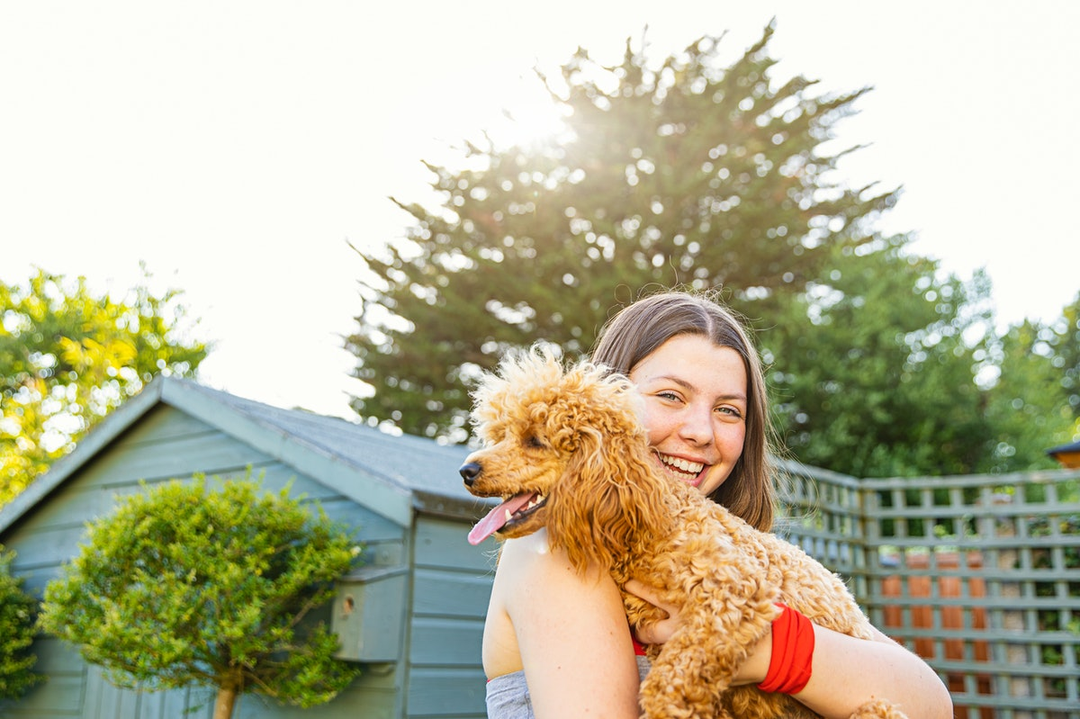 Happy young woman holding her dog, taking a pic to post with dog point of view Instagram captions.