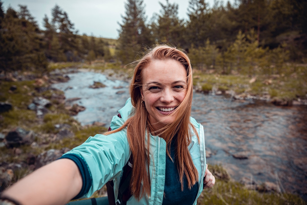 Young woman taking a selfie in front of a stream on a hike before posting the pic with camping Instagram captions.