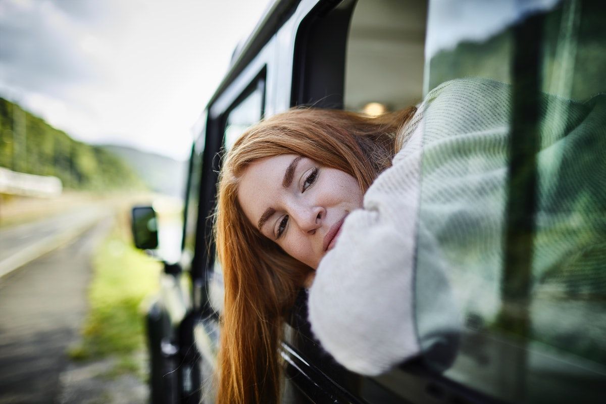 Teenage girl looking out of window of off-road vehicle in Tennessee before posting a pic on Instagram with a Nashville caption.
