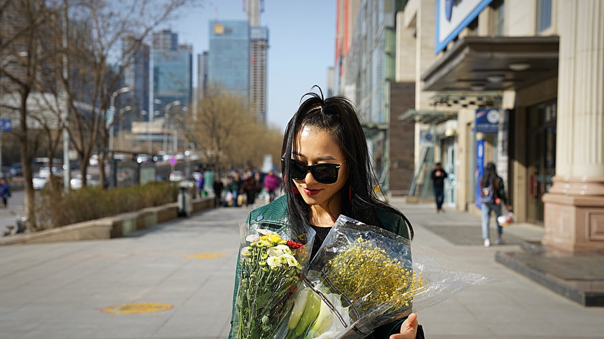 Young woman holding a bouquet of flowers, ready to post on Instagram with flower quotes and captions...