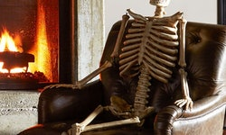 fake halloween skeleton from pottery barn sitting on chair indoors by fireplace