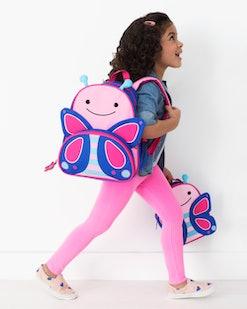 little girl wearing a butterfly backpack
