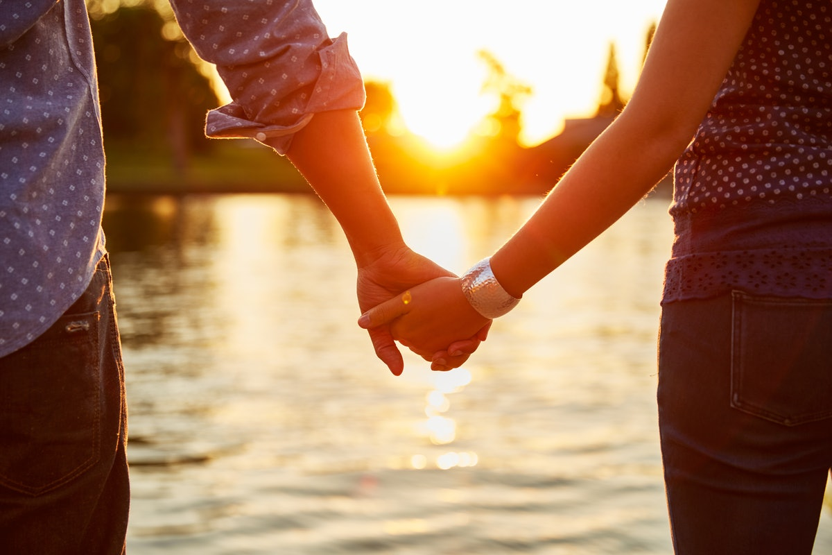 Young couple holding hands with each other at sunset before posting a pic on Instagram with romantic...