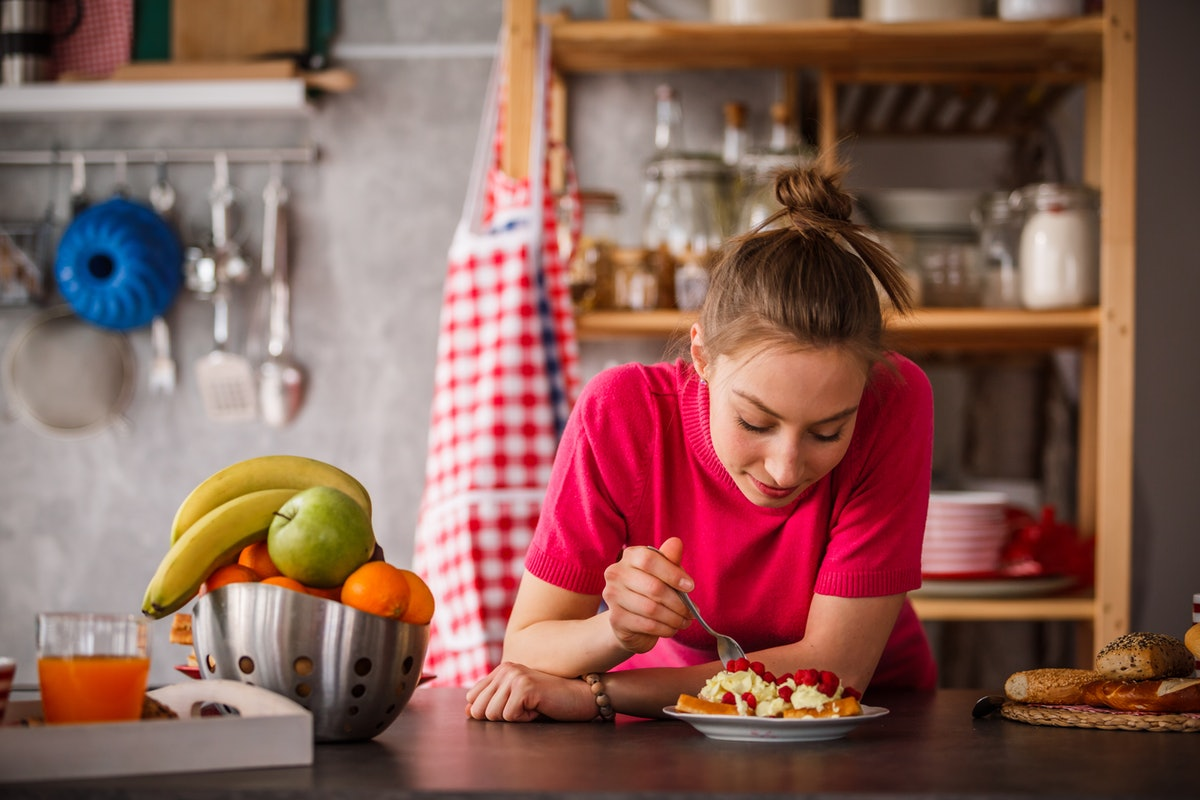 Young woman eating breakfast in her kitchen before posting a foodie pic on Instagram with waffle puns, quotes, and captions.