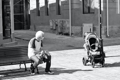 A masked older man keeps a safe distance from a baby in a stroller. There is still hope for families...