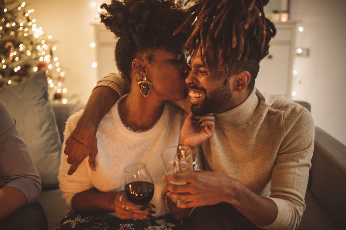 Young couple kissing while holding Champagne flutes on New Year's Eve before posting a pic on Instag...