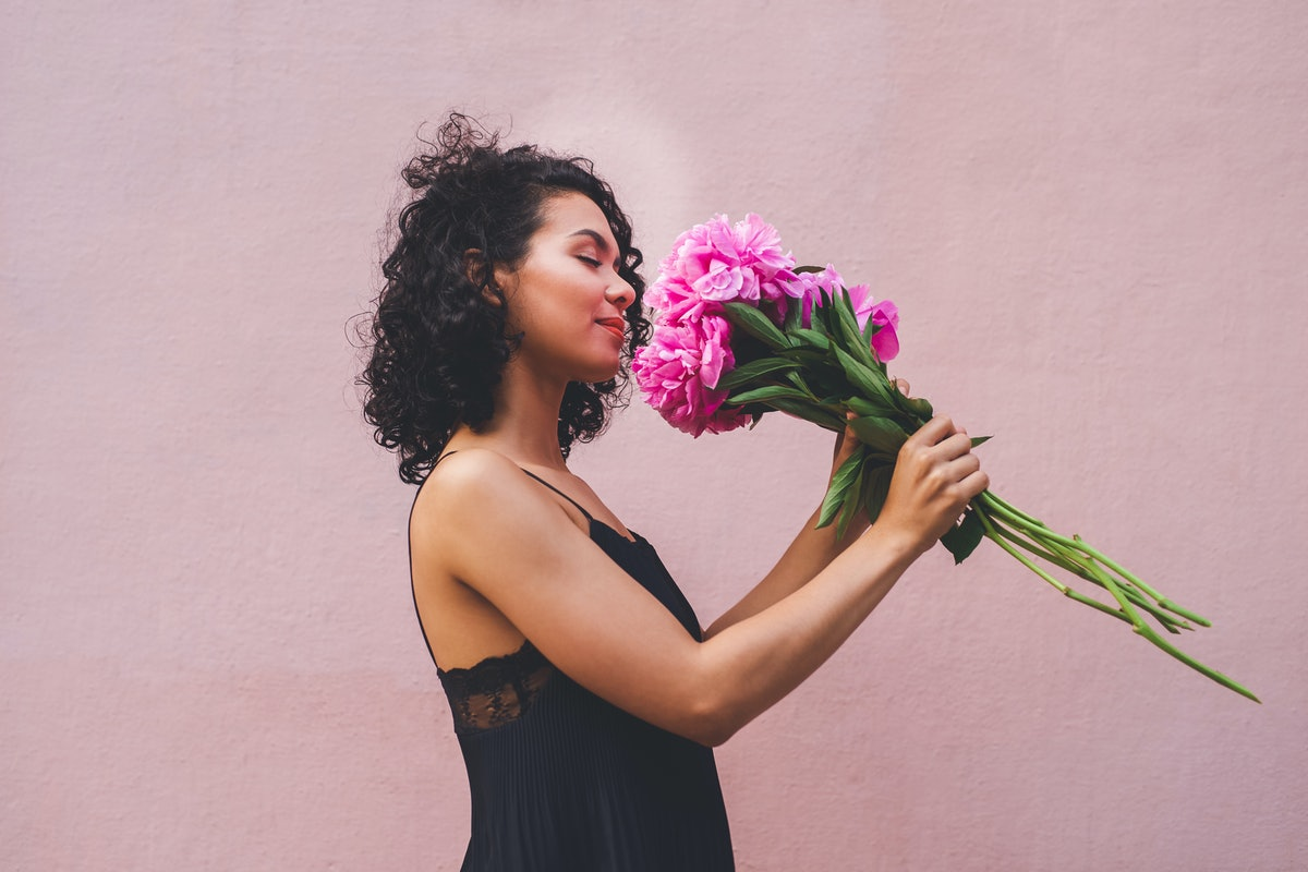 Young woman smelling a bouquet of flowers before posting a pic on Instagram with flower quotes and c...